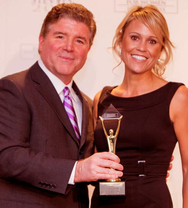 Image of Michael Gallagher, president and founder of the Stevie Awards, presents Marnie Oursler of Marnie Homes with her Gold Stevie
